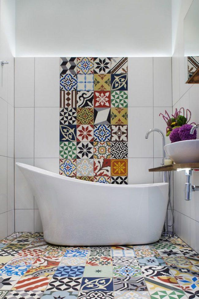 Le panneau de carreaux multicolores est soutenu par le même carreau sur le sol de la salle de bain