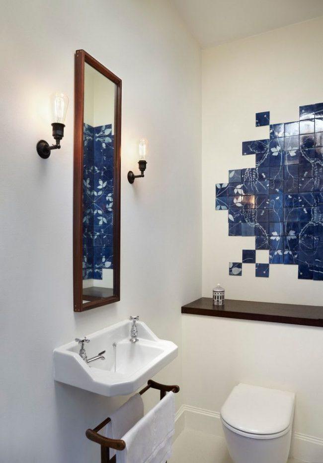 Un panneau de carreaux bleu foncé contraste avec le fond d'une salle de bain blanche
