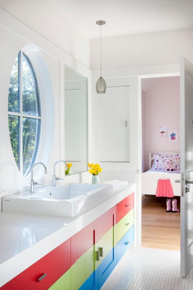 Salle de bain lumineuse pour un enfant, où le lavabo est encastré dans un tube coloré