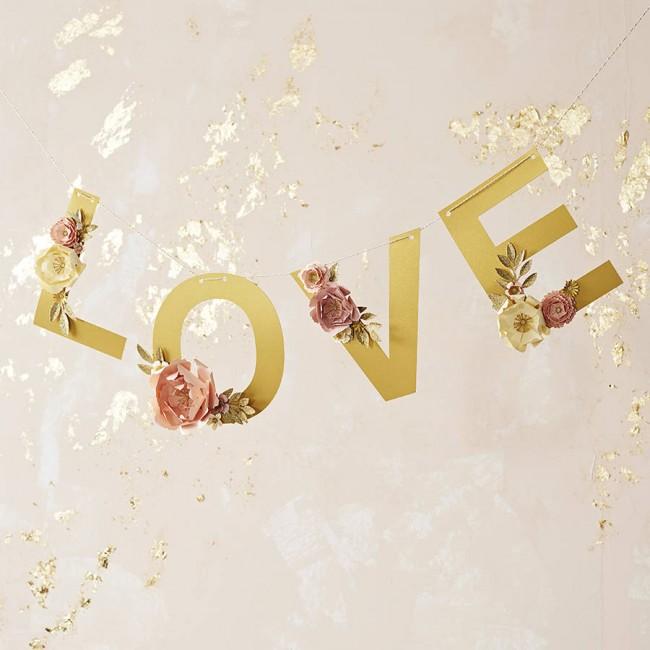 Les chiffres, les mots et autres sur les murs ne sont pas du tout des motifs dépassés.  Sur la photo, une décoration de fête de fiançailles inégalée faite de feuilles d'or et de fleurs en papier