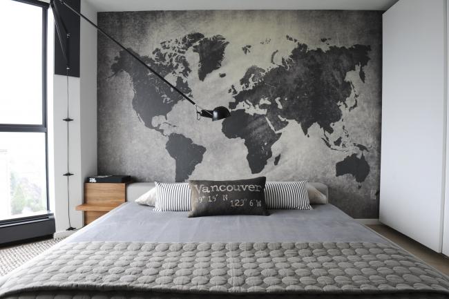 Chambre à coucher de style loft.  La carte graphique du monde mur à mur met l'accent sur l'intérieur monochrome