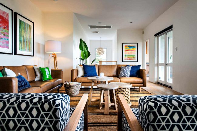 Ornements noirs et blancs sur le rembourrage des chaises et des coussins dans le salon spacieux d'une maison privée