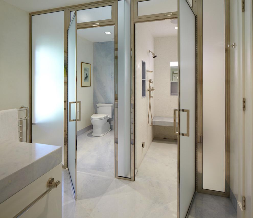 Petite salle de bain lumineuse avec portes en verre dépoli